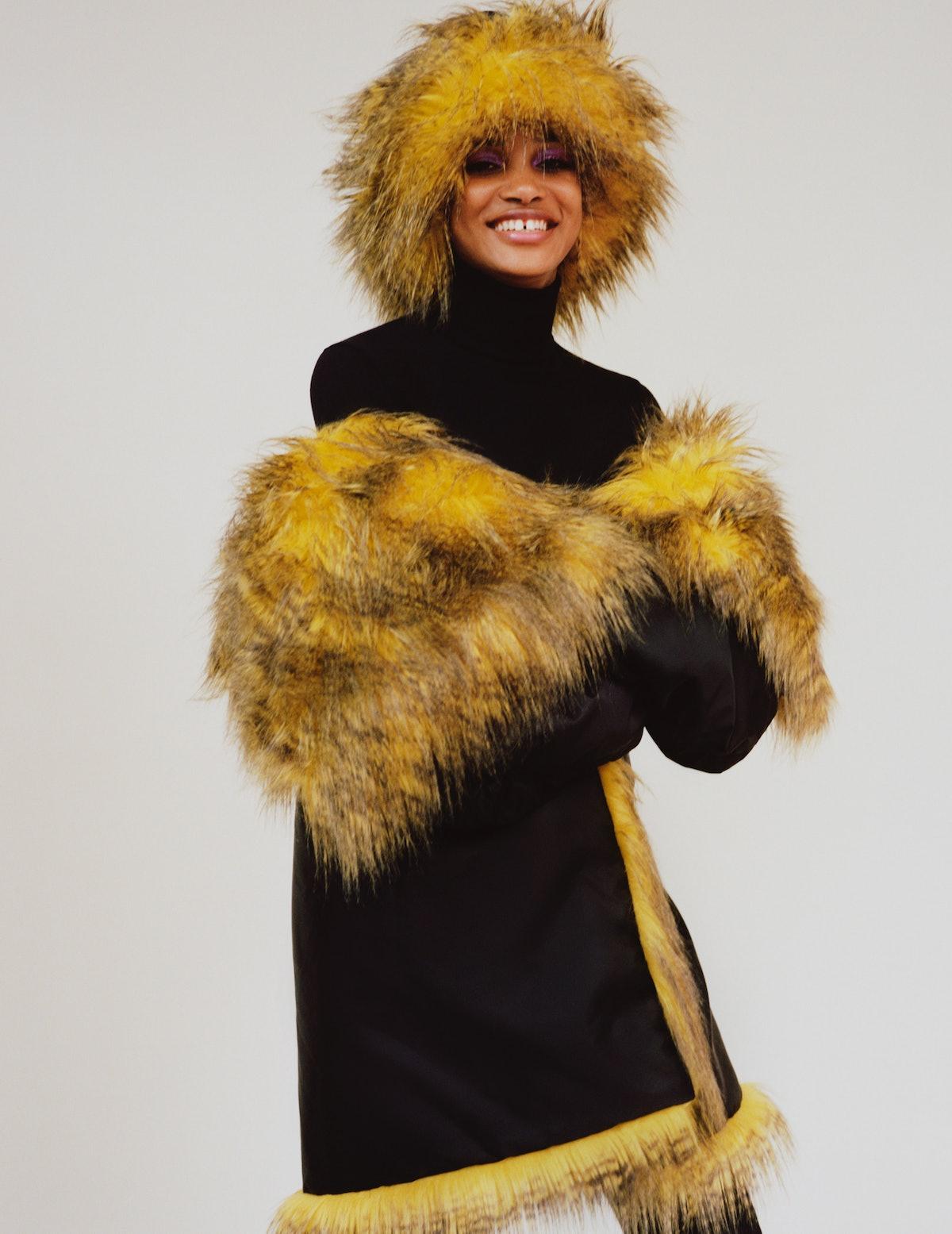Amandine Guihard wears a Prada jacket with detachable hood (worn as hat), long johns, and boots.