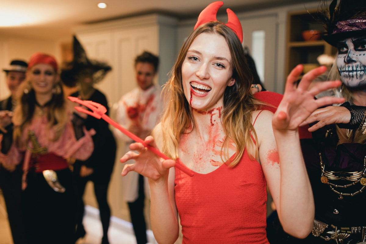 Young blonde woman in devil costume, in need of caption for posing in her Halloween outfit on Instag...