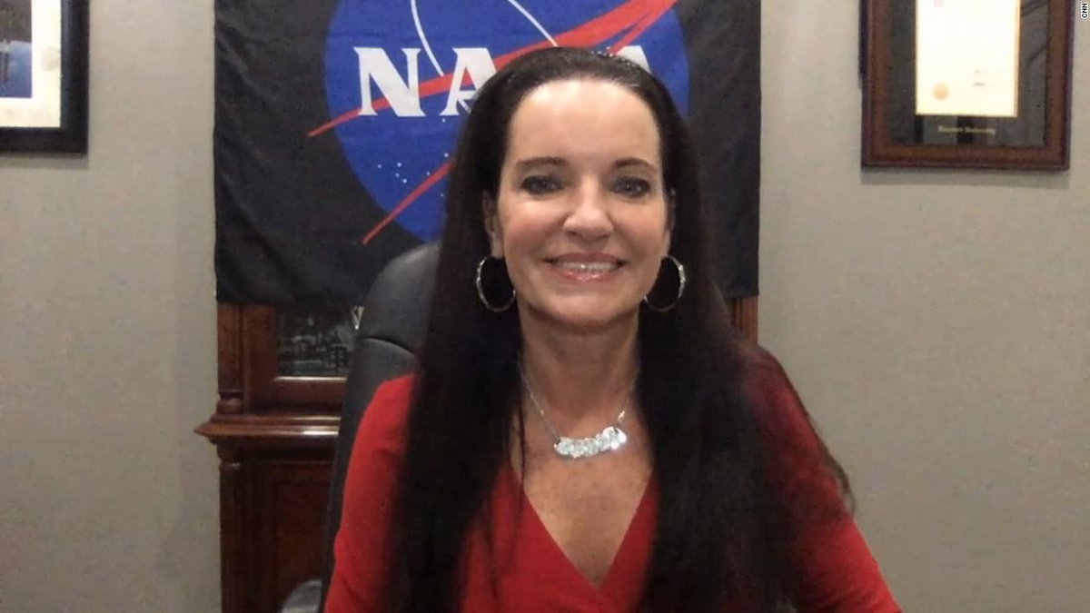 Smiling woman with a NASA flag in the background.