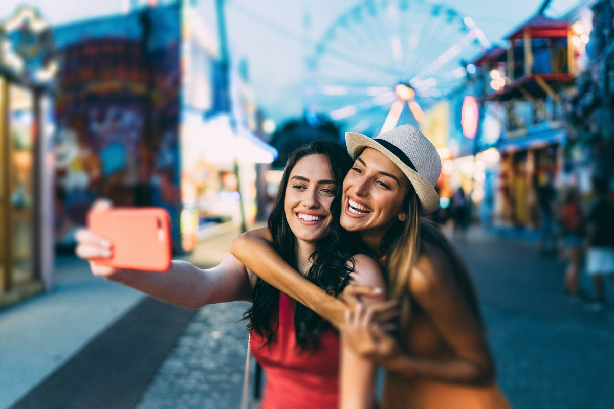 Friends taking a selfie at a fall fair before posting a photo on Instagram with a cute carnival capt...