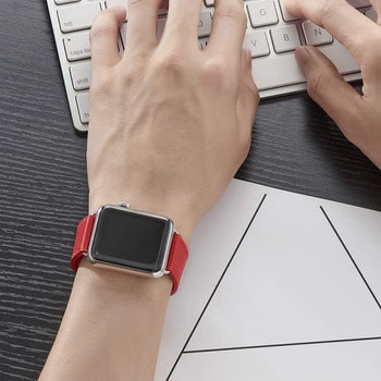 apple watch with bright red band on person typing on keyboard