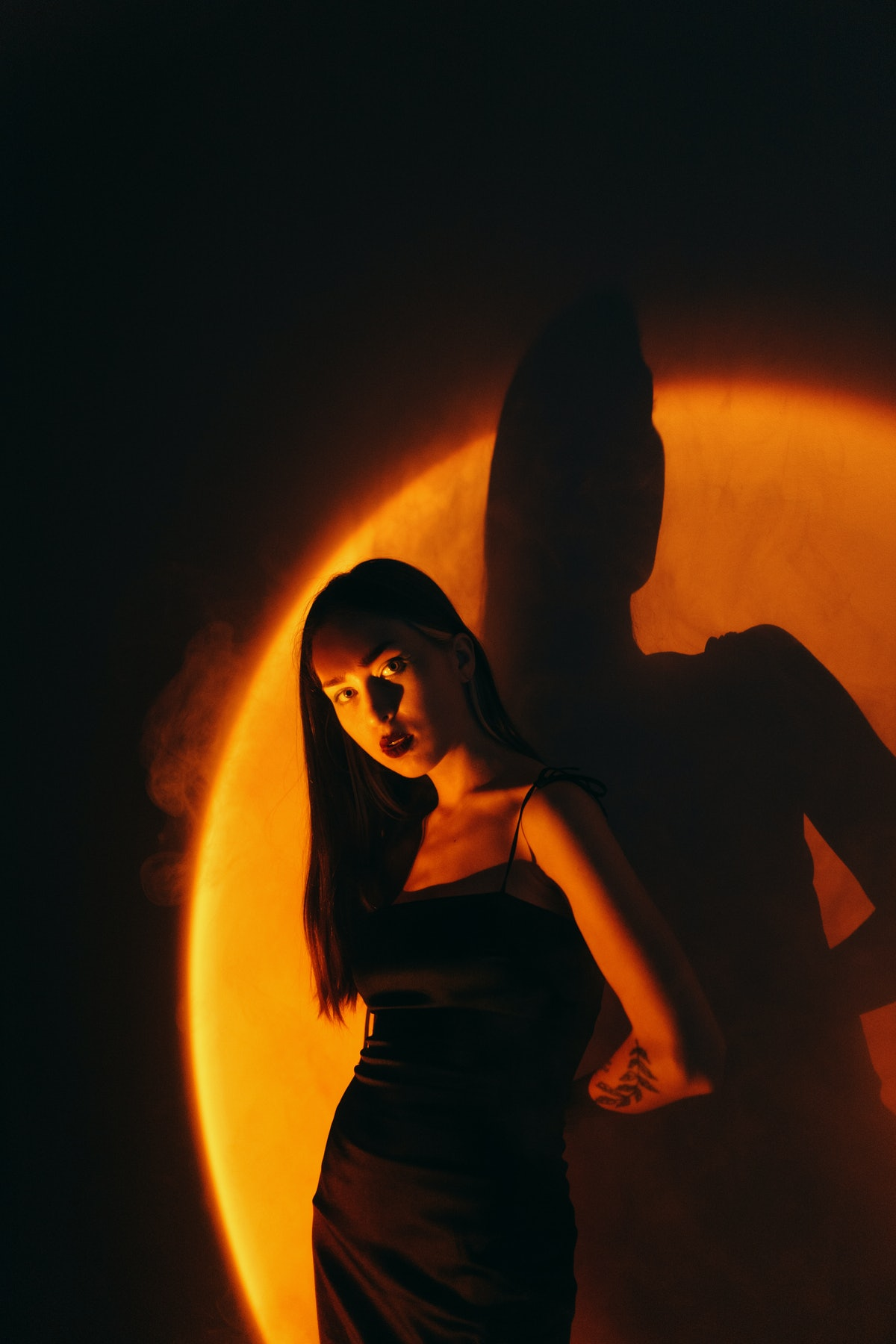 Young woman in black dress standing under the orange light, affected by the September 2021 new moon ...