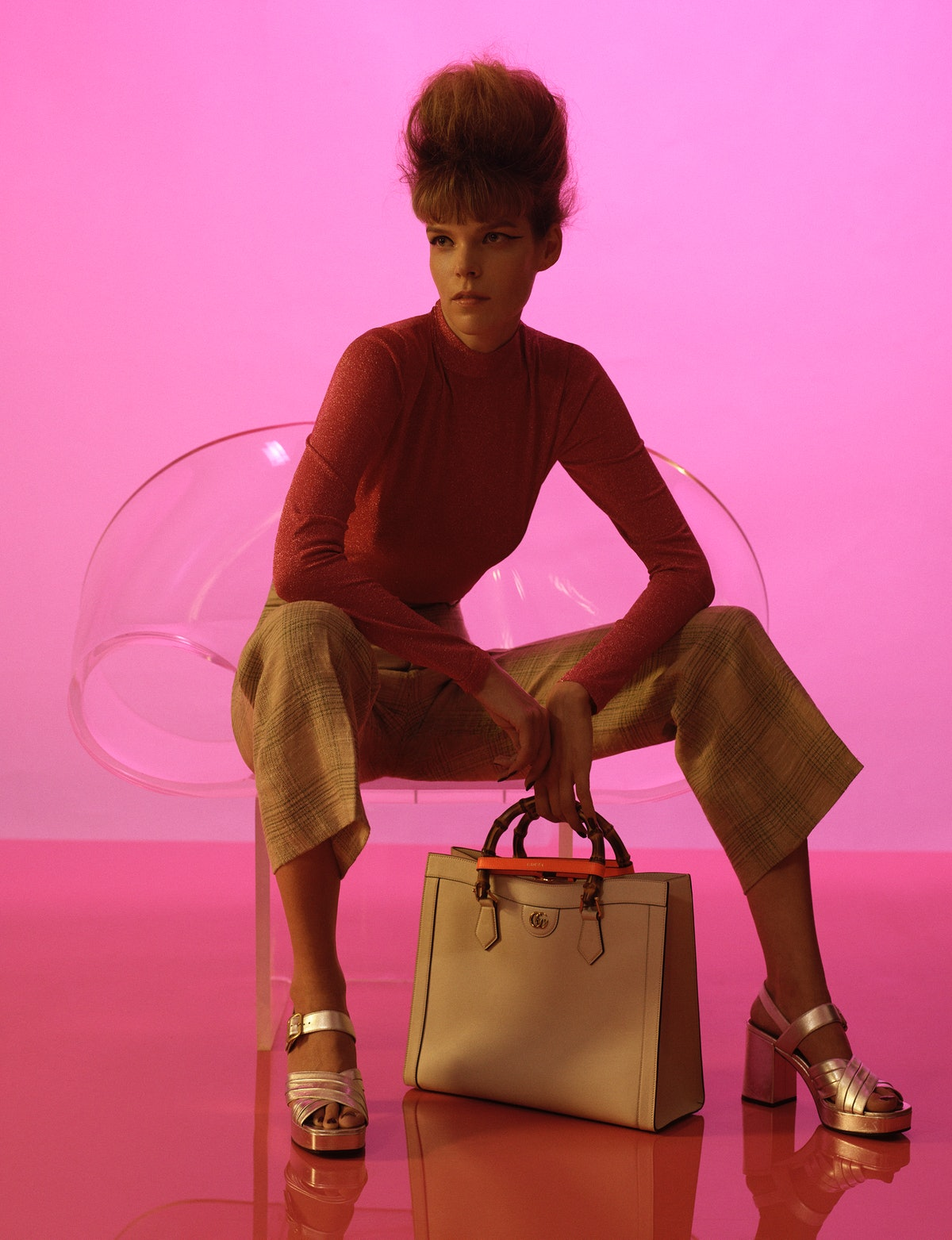 Meghan Collison wears a Gucci turtleneck, pants, bag, and sandals.