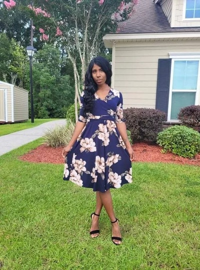 Woman standing outside; modeling navy blue a-line wrap dress with floral print