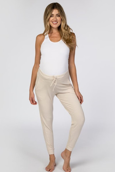 Woman standing, modeling cream-colored joggers