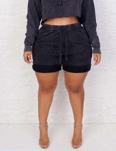 Model wearing black crop sweatshirt and black shorts with drawstring waist