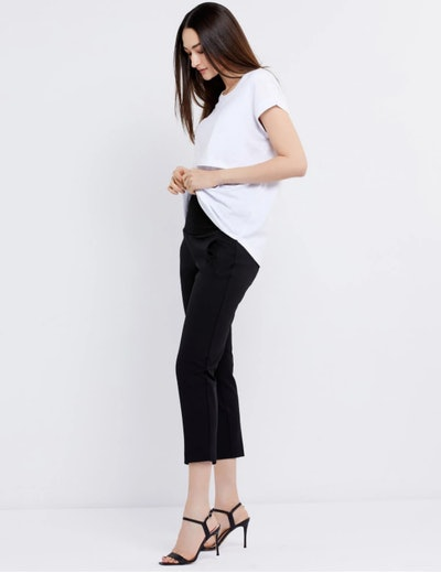woman standing sideways wearing white top and black crop pants