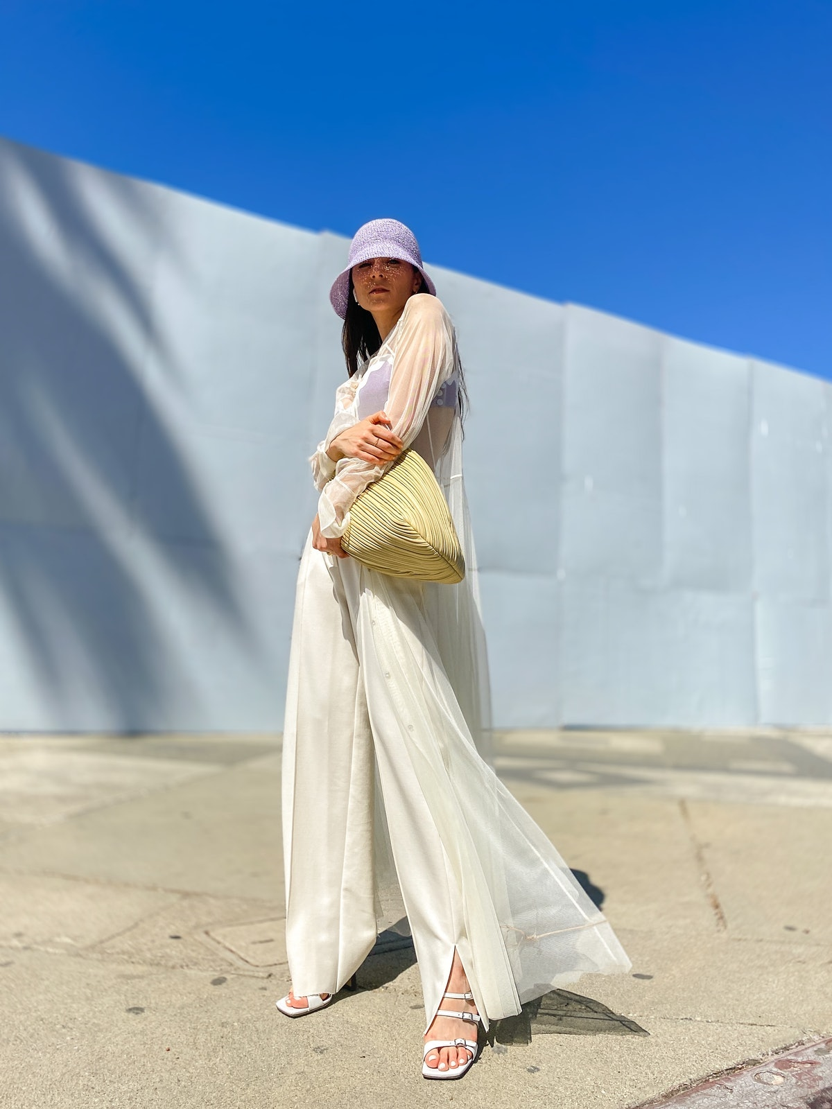 Julia Comil wears a White Tulle shirt dress, high waisted oversized white pants, a mauve pale purple...