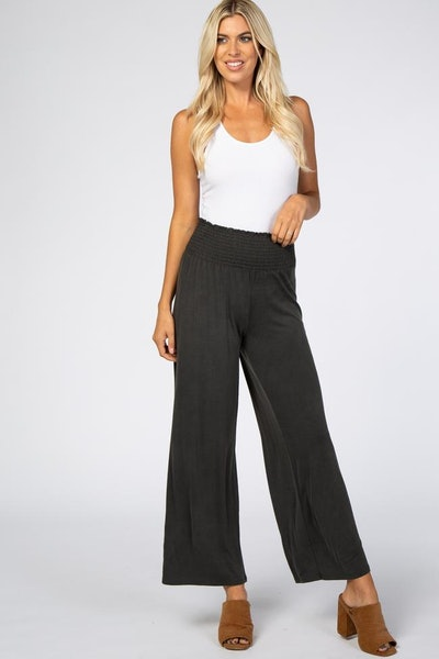 Woman standing; modeling black smock waisted flowy pants