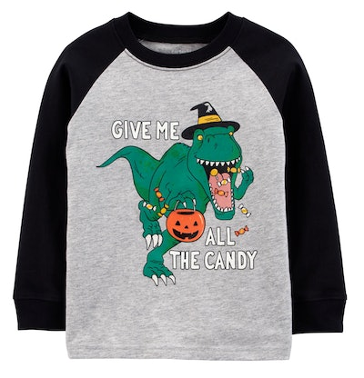 Image of a shirt with a green dinosaur on it, holding a trick-or-treating pumpkin candy bucket.
