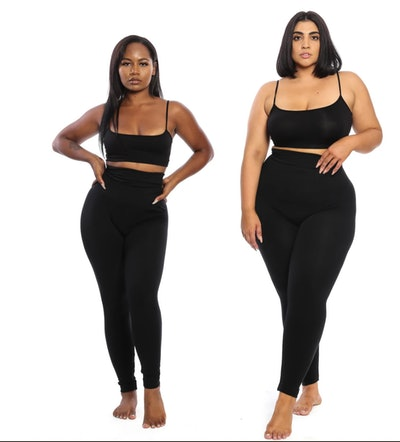 Two women standing in matching black bras and high-waist leggings