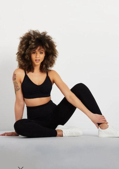 Woman in crop top and black leggings, sitting