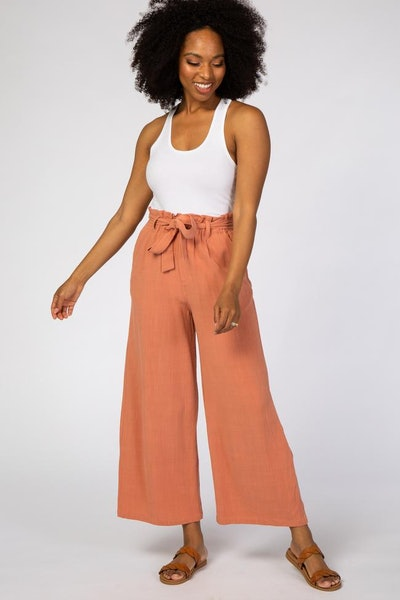 Woman wearing white tank top, modeling wide-leg paperbag pants in coral