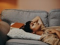 Young woman laying on the couch wondering does February mess up your period.