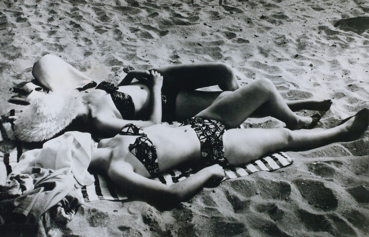 two women in hats and bikinis lie on a beach