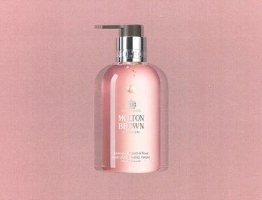 a bottle of Molton Brown's rhubarb and rose hand soap against a pink background