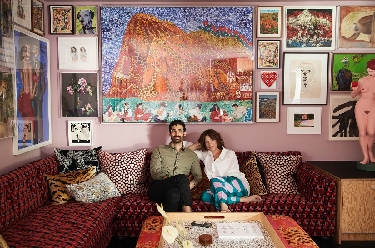 David Kordansky and Mindy Shapero seated on a red couch surrounded by artwork