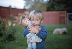blond baby boy holding a doll