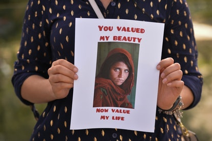 A protester holds the famous Afghan Girl photo, a 1984 photographic portrait of Sharbat Gula by phot...