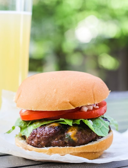 Jalapeno Bacon Cheddar burger on a plate with a glass of lemonade behind it