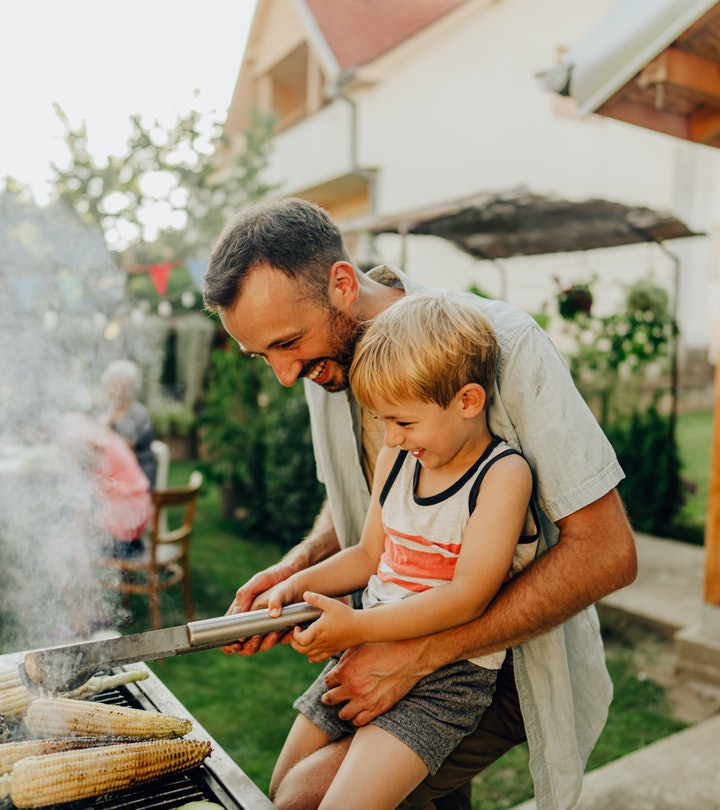 Father and young son, smiling, grilling together