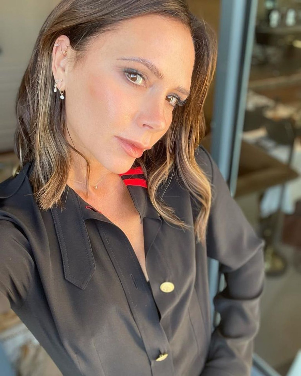 Victoria Beckham wears black military detail pleated dress from her brand, Victoria Beckham, on Inst...