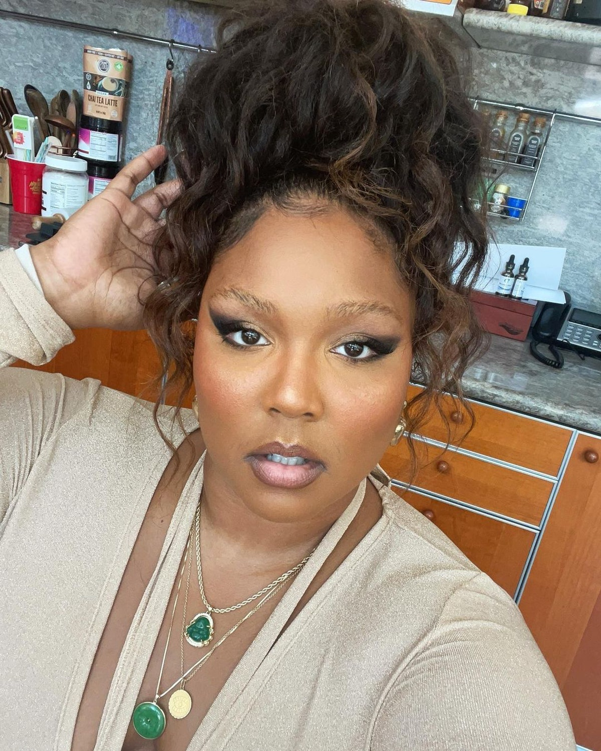 Lizzo with messy bun, winged liner, and beige-and-emerald outfit