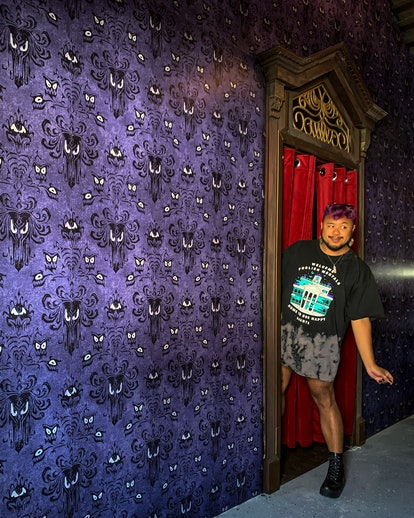 Francis Dominic stands in an Airbnb inspired by Disney's Haunted mansion with Haunted Mansion wallpa...
