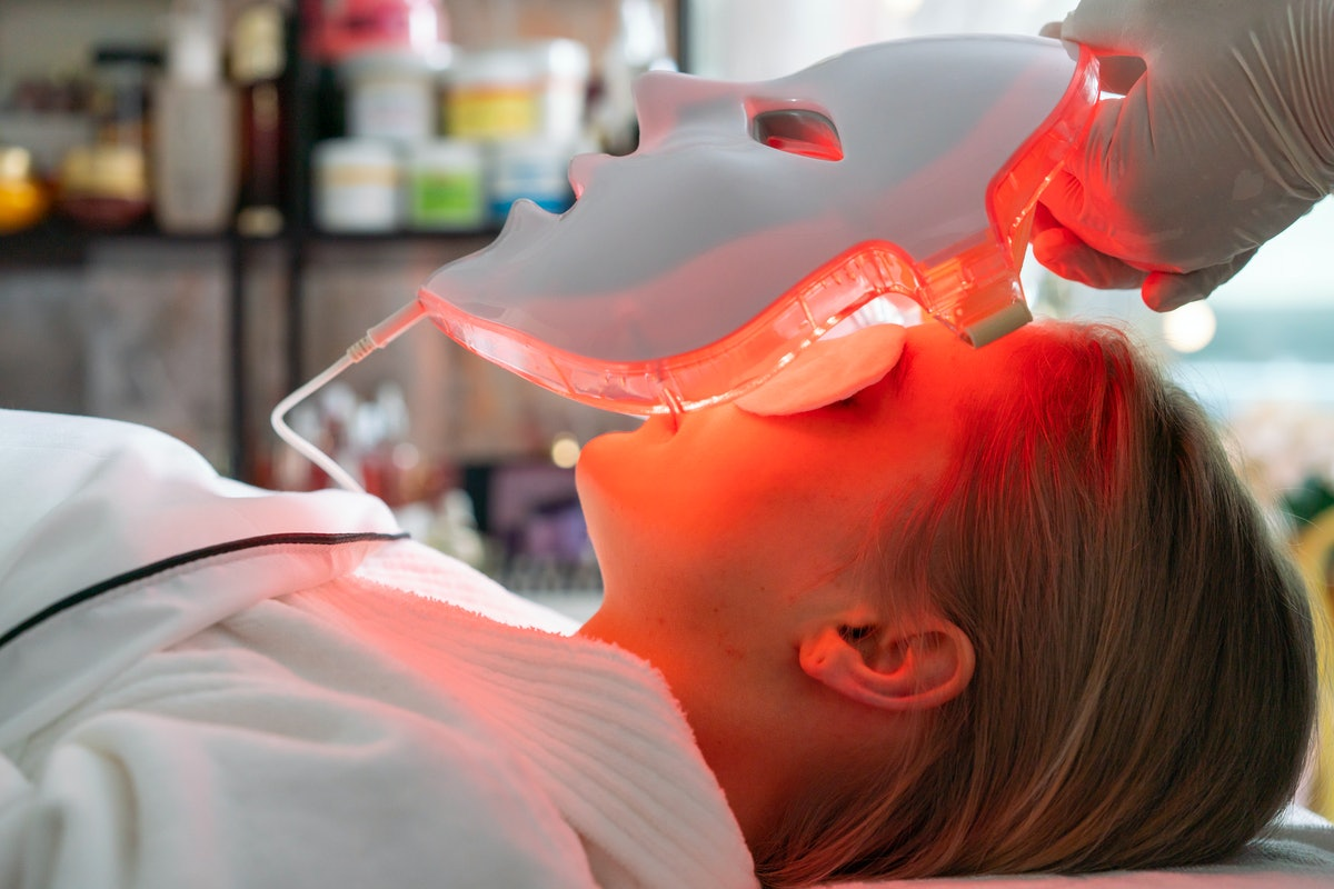 Woman getting LED light treatment from a doctor