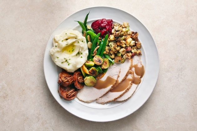 Plate of thanksgiving dinner with turkey, mashed potatoes, brussels sprouts, and more