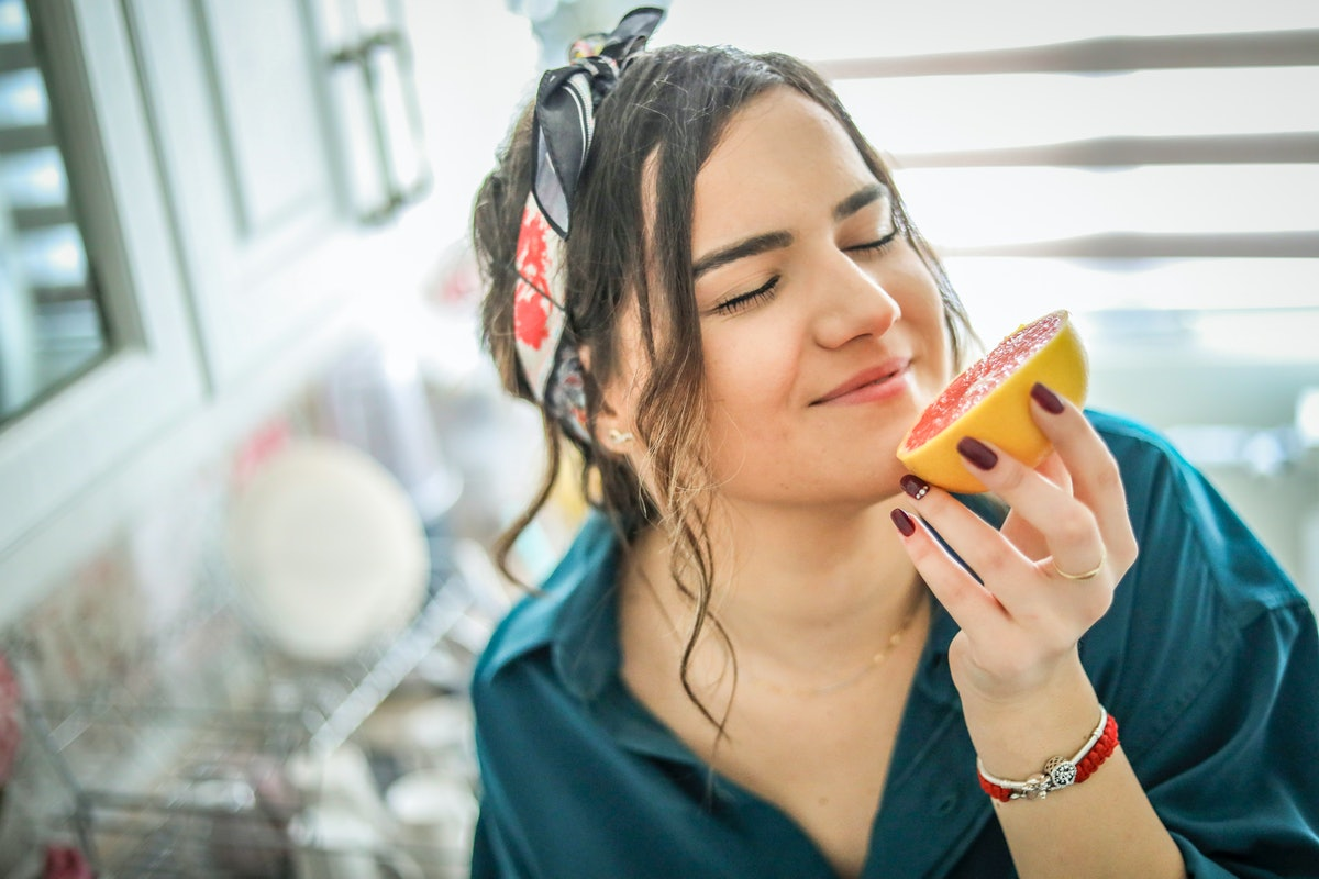 Young woman eating grapefruit to show whether certain foods can change how your vagina tastes.