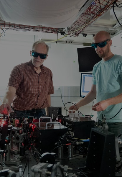NIST physicists John Bollinger (left) and Matt Affolter adjust the laser and optics array used to tr...
