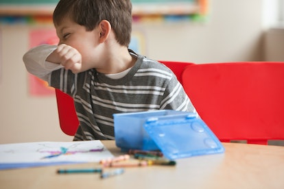 A child at school sneezes into his elbow while drawing with crawyons.