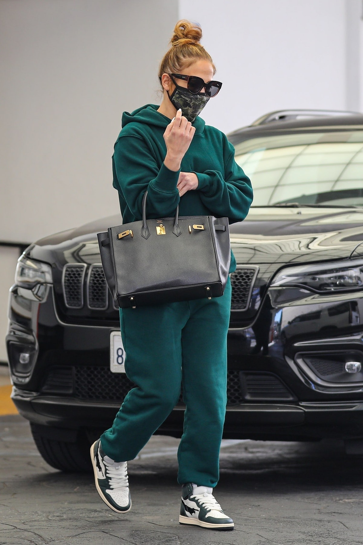 Jennifer Lopez wears matching emerald green sweatshirt and sweatpants from Les Tien in Beverly Hills...