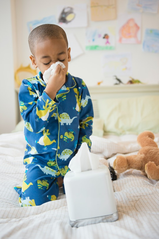 A Black boy wearing pajamas blows his nose with a tissue while sitting on a bed.