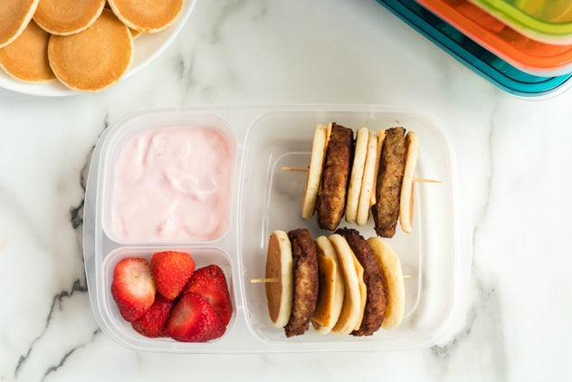lunch box with yogurt and pancakes and sausage