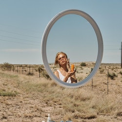 Woman in desert with mirror and skin care products