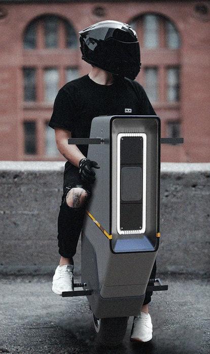 A person sits on the BAIKU vehicle wearing a black helmet. EV. Electric vehicles. EVs.