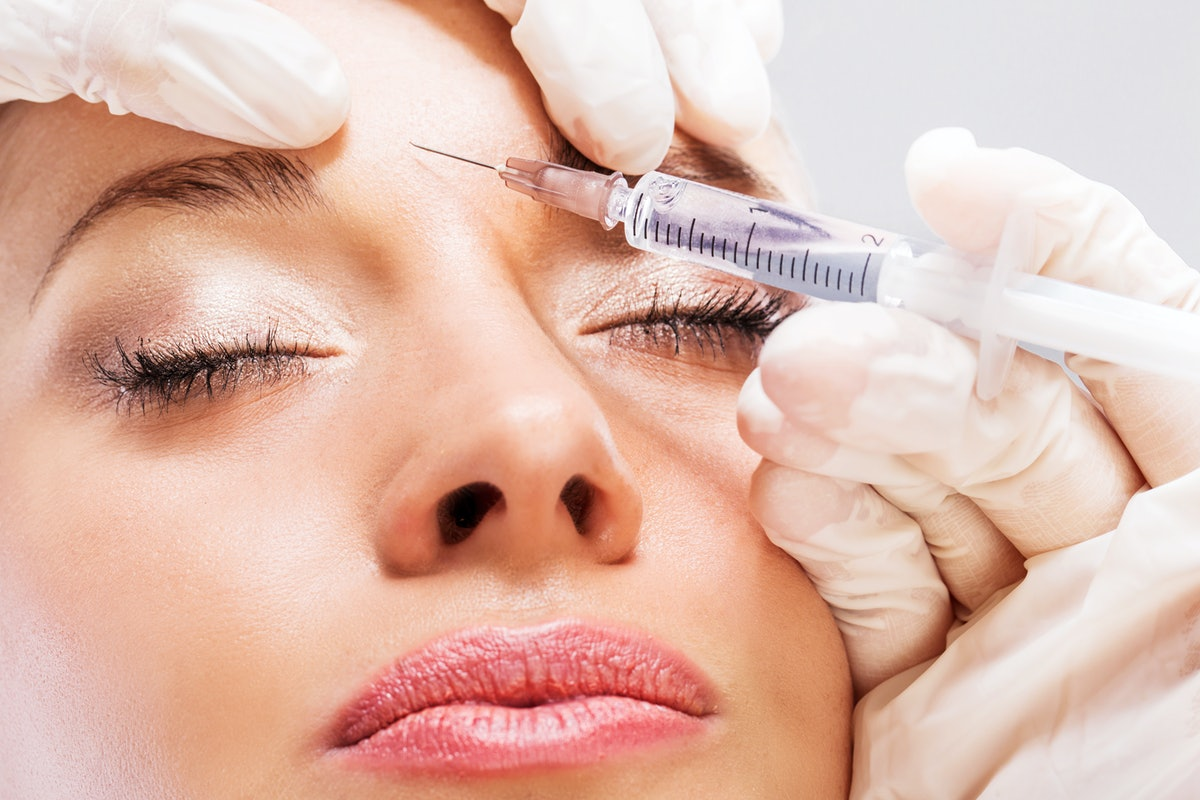 Woman getting a Botox injection in forehead