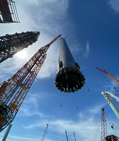 SpaceX Starship Super Heavy booster being lowered onto platform