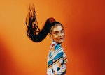 A young Black woman flips her long ponytail and killer makeup, looking ready to go back to school wi...