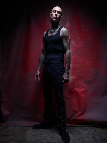 A full-length image of Travis Barker standing in front of a red backdrop.