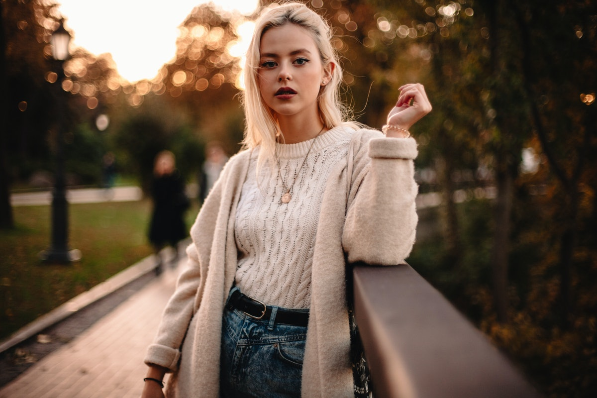 Young woman in a cableknit sweater during the 2021 fall equinox, which will affect her zodiac sign m...