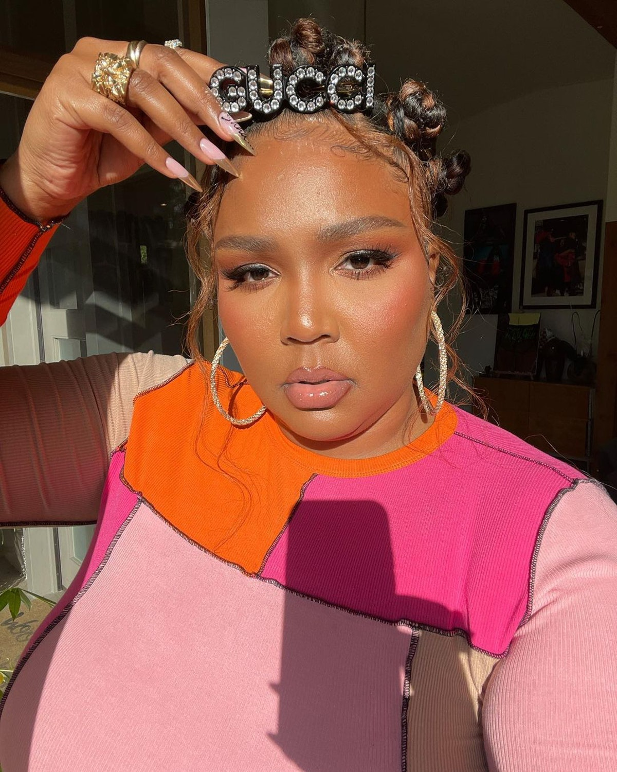 Lizzo selfie with Bantu knots, Gucci barrette, and gold nails