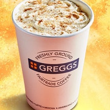 A greggs paper cup against an orange and yellow swirled background. The cup is filled with creamy fo...