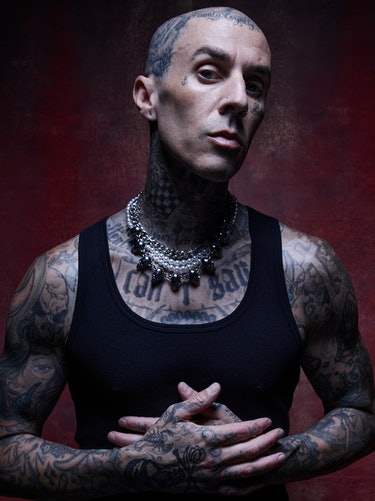 NYLON cover star Travis Barker poses with his hands against his chest.