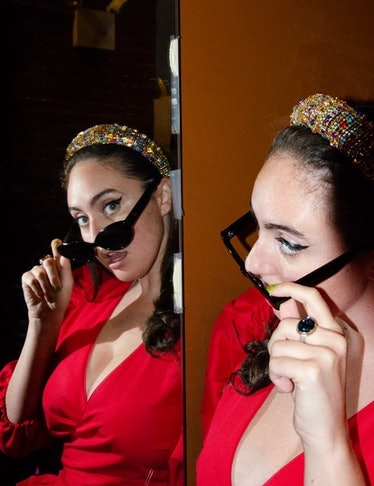 the comedian Catherine Cohen wearing a red dress and black sunglasses looking at herself in the mirr...