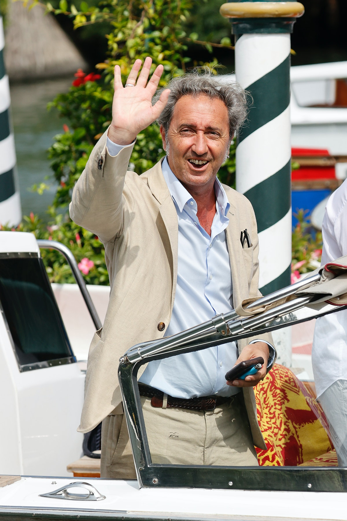Paolo Sorrentino in a tan suit waving