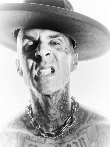 NYLON cover star Travis Barker shows his teeth while wearing a wide-brimmed hat and posing for a clo...