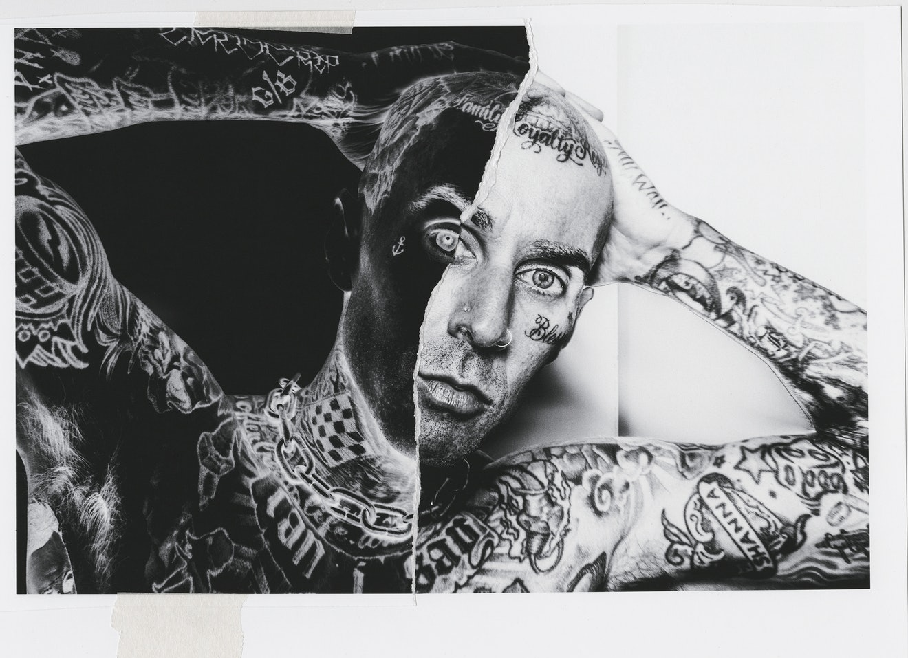 A black and white image of Travis Barker standing with his hands behind his head.